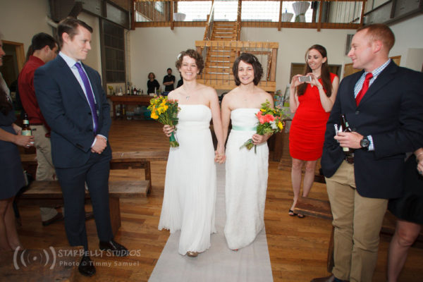 Two brides, both in white dresses, walk up their wedding aisle together holding bouquets