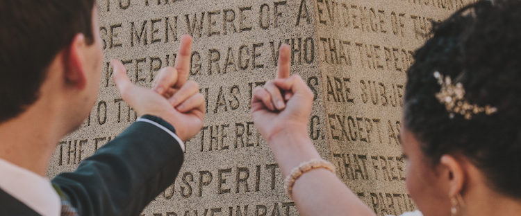 A bride and groom flash their middle fingers at a confederate memorial. Amanda and Steve Say Fuck the Confederacy - Photo by Amanda Summerlin Photgraphy