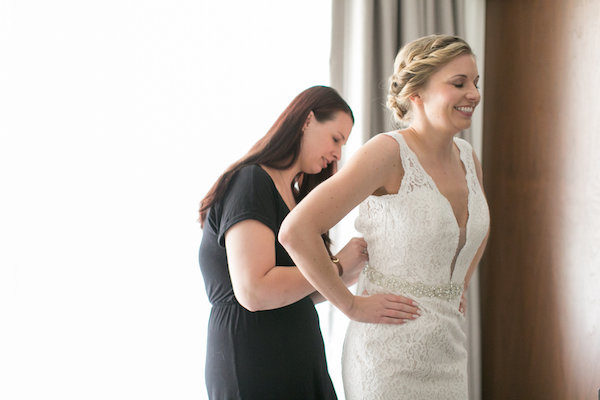 Aisle Less Traveled associate coordinator Kelly zips Kiley into her wedding gown. Photo: Christy Tyler Photography