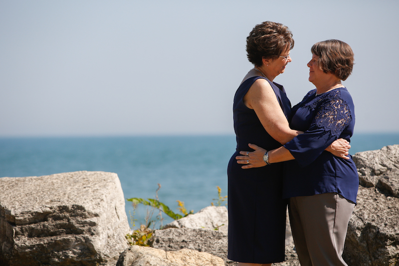 Mary and Pam, just married and both wearing navy, embrace along the rocky shore of Lake Michigan in Evanston, Illinois.