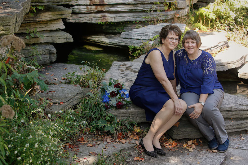 Mary and Pam, both wearing navy, are seated on some wide, flat rocks at Chicago's Lily Pool