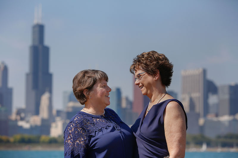Pam, left, in a navy blouse; and Mary, right, in a navy sleeveless dress, stand looking into each other's eyes against the Chicago skyline and lakefront.
