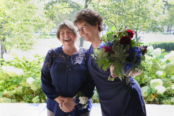 Pam, left, in a navy blue top and khaki trousers stands with Mary, right, in a navy blue wrap dress during their Chicago elopement. Pam wears a wrist corsage; Mary holds a colorful bouquet. Chicago Elopement Mary Pam Wedding 109 Evanston Ceremony