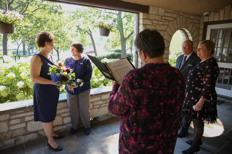 Two women, both wearing navy, stand at the back of a stone porch overlooking trees and greenery. In the foreground, officiant Anita Vaughan conducts the wedding ceremony. Two wedding guests stand and observe.