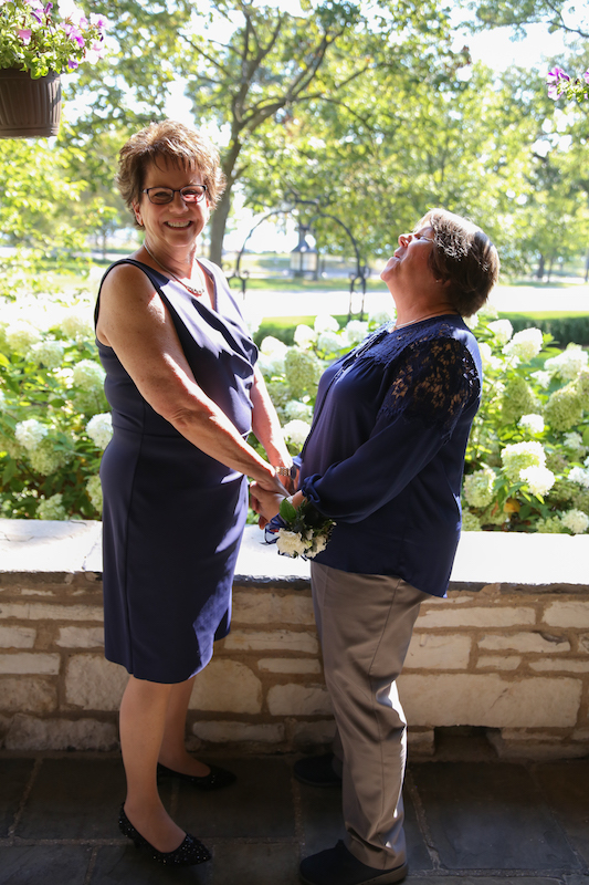 Mary, in a navy dress, and Pam, in a navy short-sleeved top and khaki trousers, stand in front of a low stone wall holding each other's hands during their wedding ceremony.