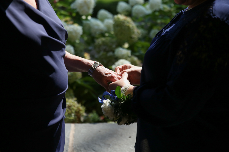 Pam, right, wearing a navy blouse, places a ring on Mary's finger. Mary stands at left and also wears navy.