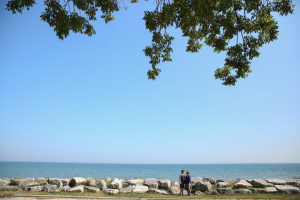 Two women, both wearing navy, stand along the rocky shore of Lake Michigan