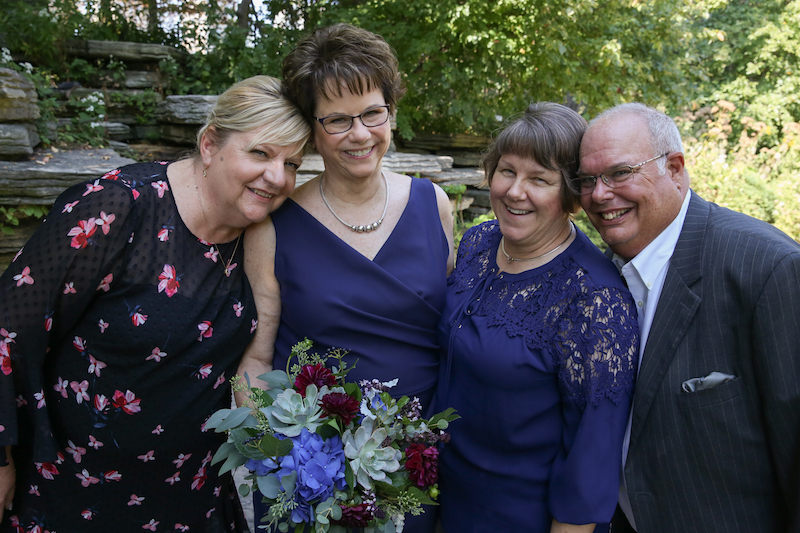A woman in a floral dress stands with Mary, in a navy dress; Pam, in a navy blouse; and a man in a suit at Chicago's Lily Pond