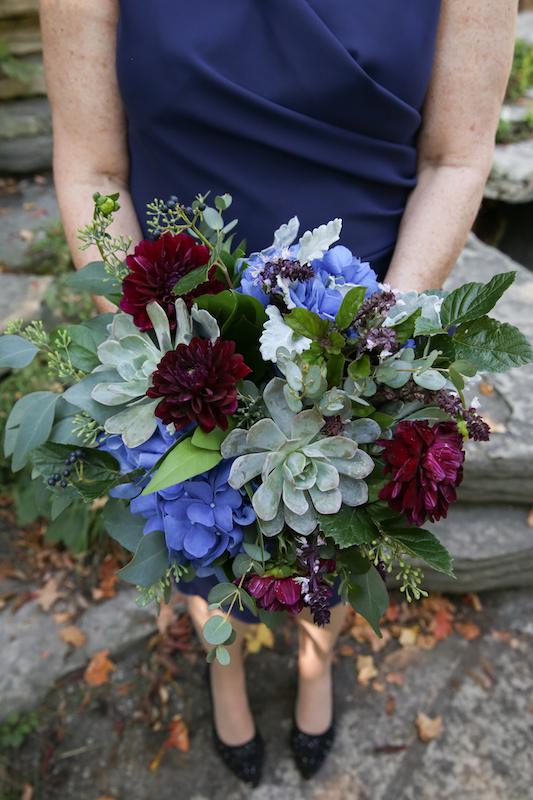 A woman wearing a navy dress holds a bouquet of flowers with bold blue and burgundy flowers and several shades of greenery.