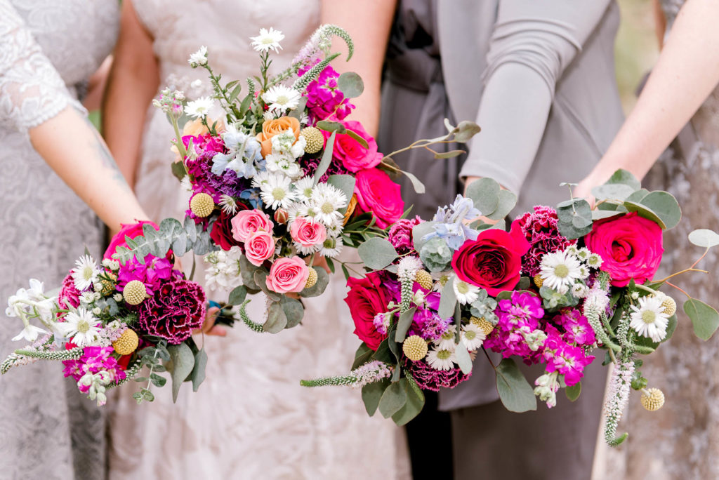 Bride and Wedding Party hold out colorful flower bouquets