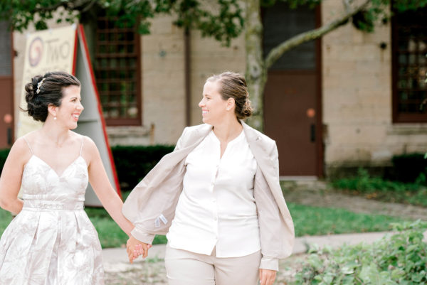 Bride in dress and Bride in suit hold hands