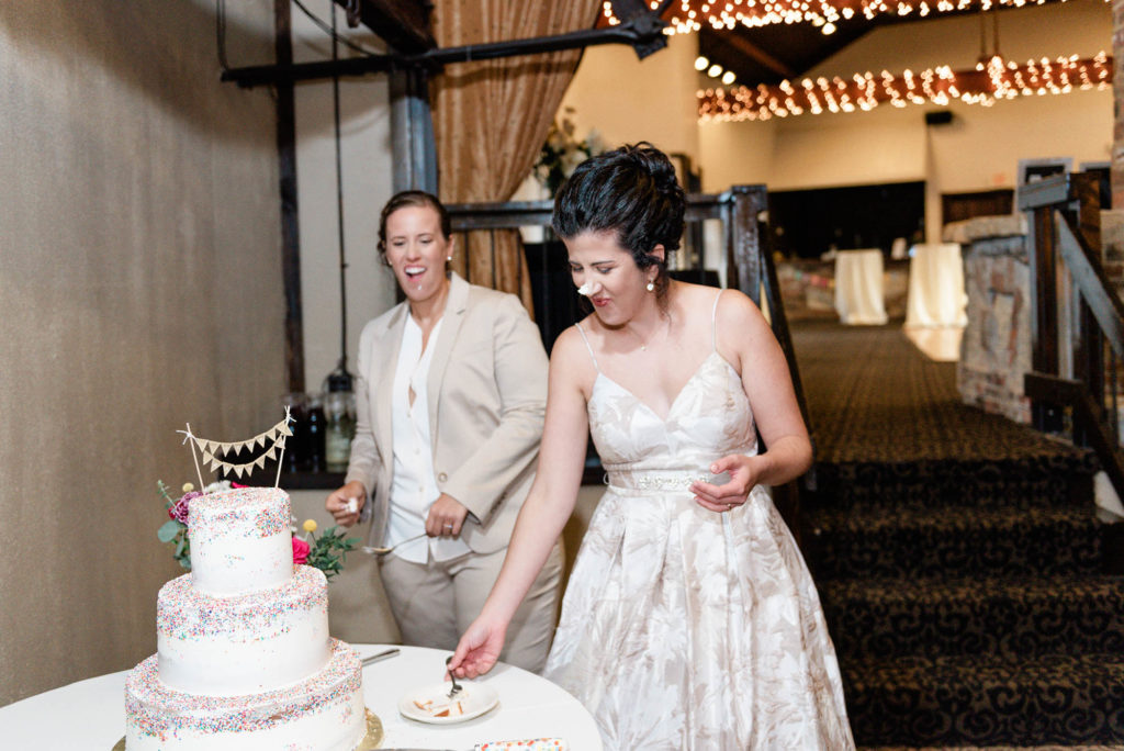 Brides smear wedding cake on each others faces