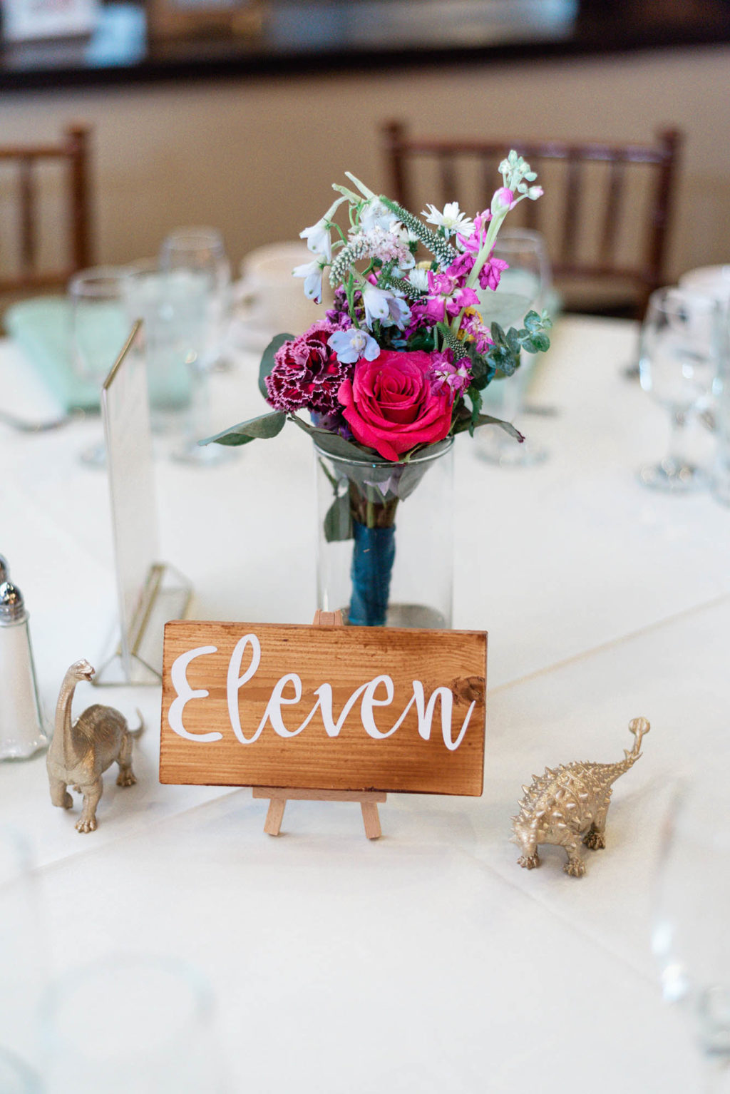 DIY wedding centerpiece colorful flowers wood painted table number gold painted dinosaurs