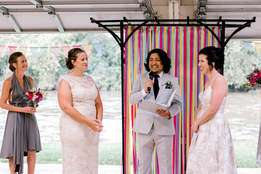 Two Brides during wedding ceremony with colorful ribbon wall backdrop