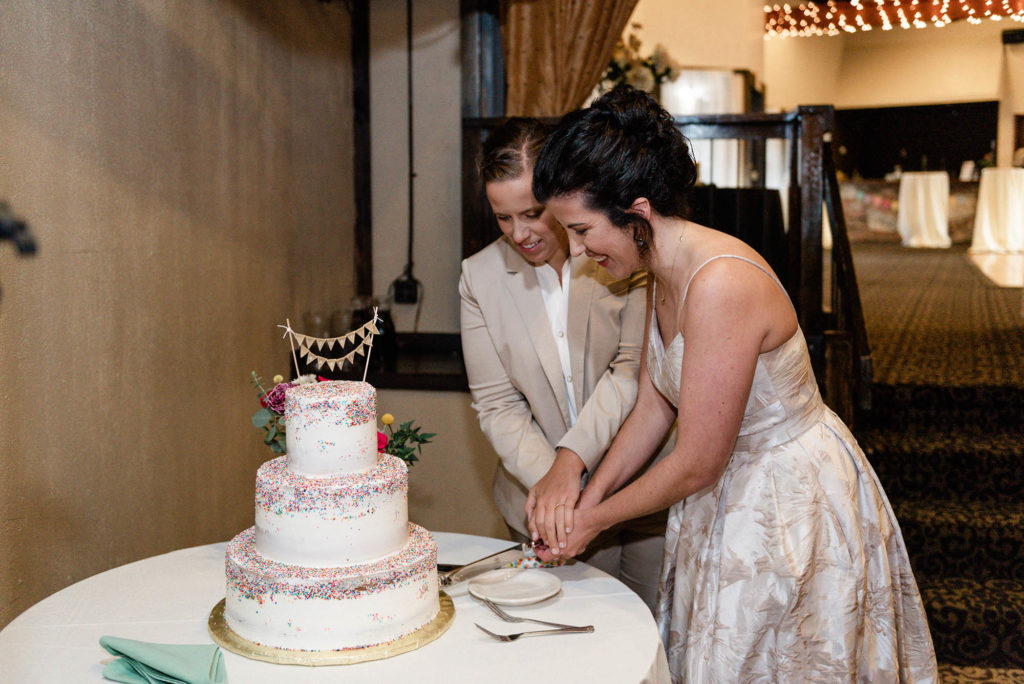 Two brides cut rainbow sprinkle wedding cake
