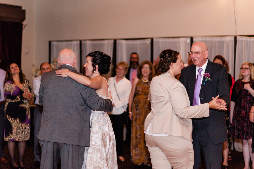 Two brides dance with their dads at wedding reception