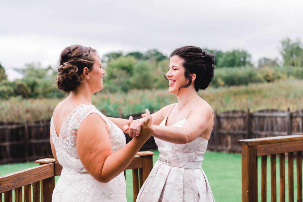Two brides holding hands and laughing