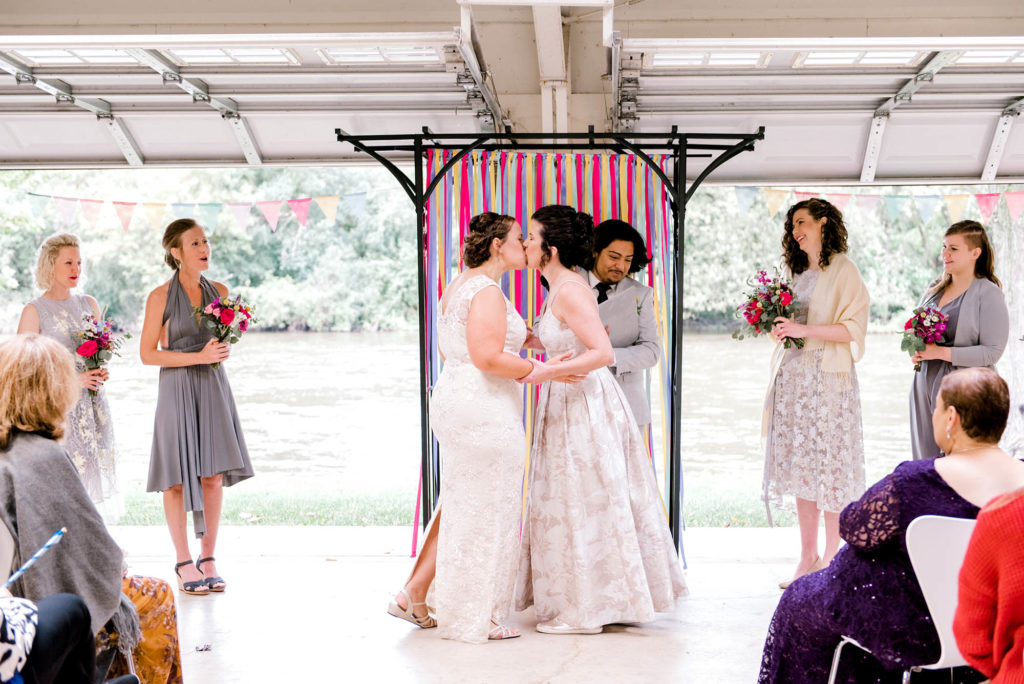 Two brides kiss at end of wedding ceremony