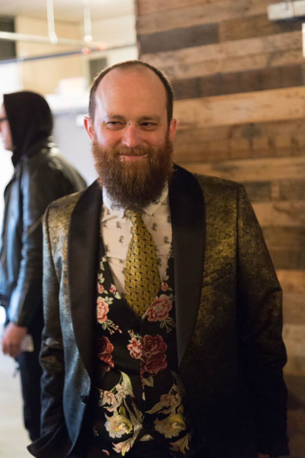 Groom with Beard and Facial Piercings Wearing Gold Floral Vest and Suit Jacket