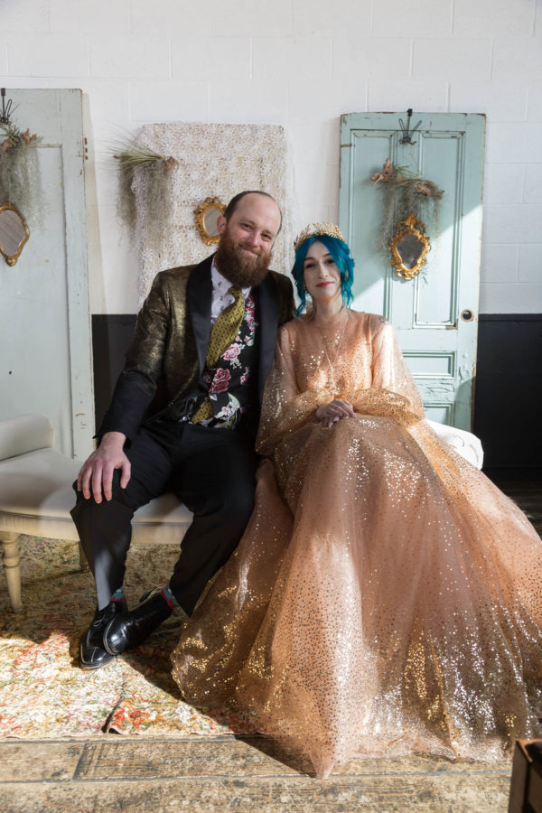 Offbeat Wedding Couple on Bench in front of Vintage Doors and Air Plants