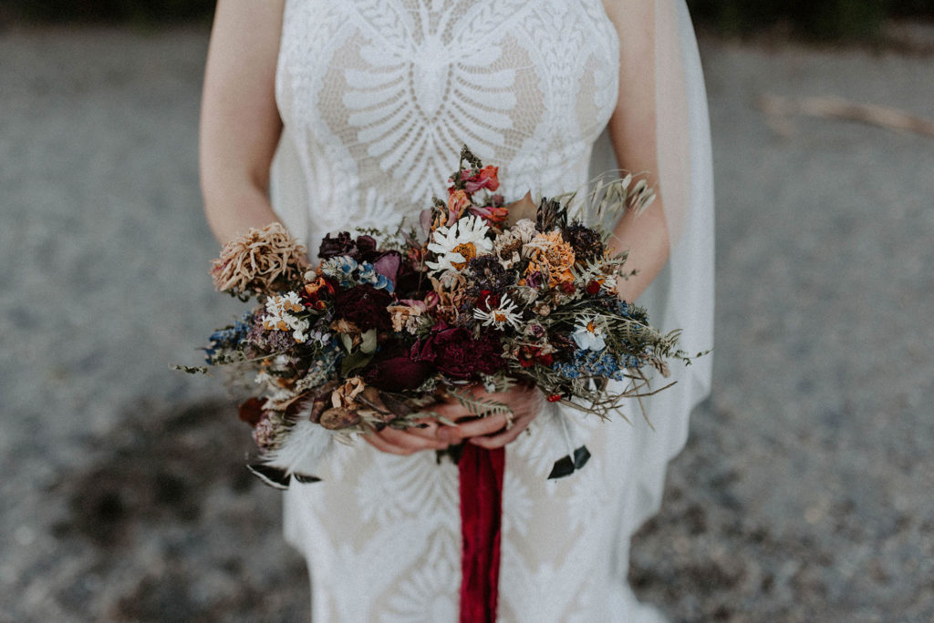 deep saturated hue bridal bouquet with red ribbon