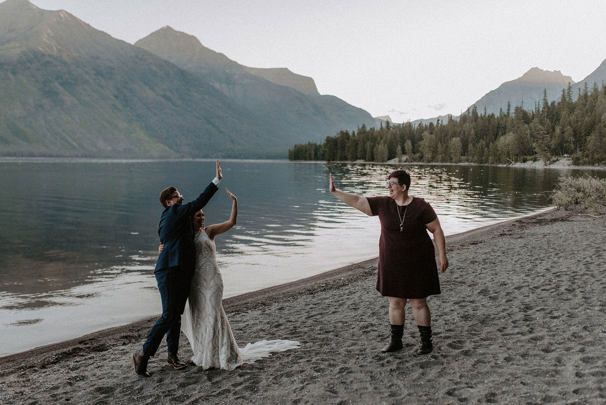 socially distant high five with two brides and wedding officiant