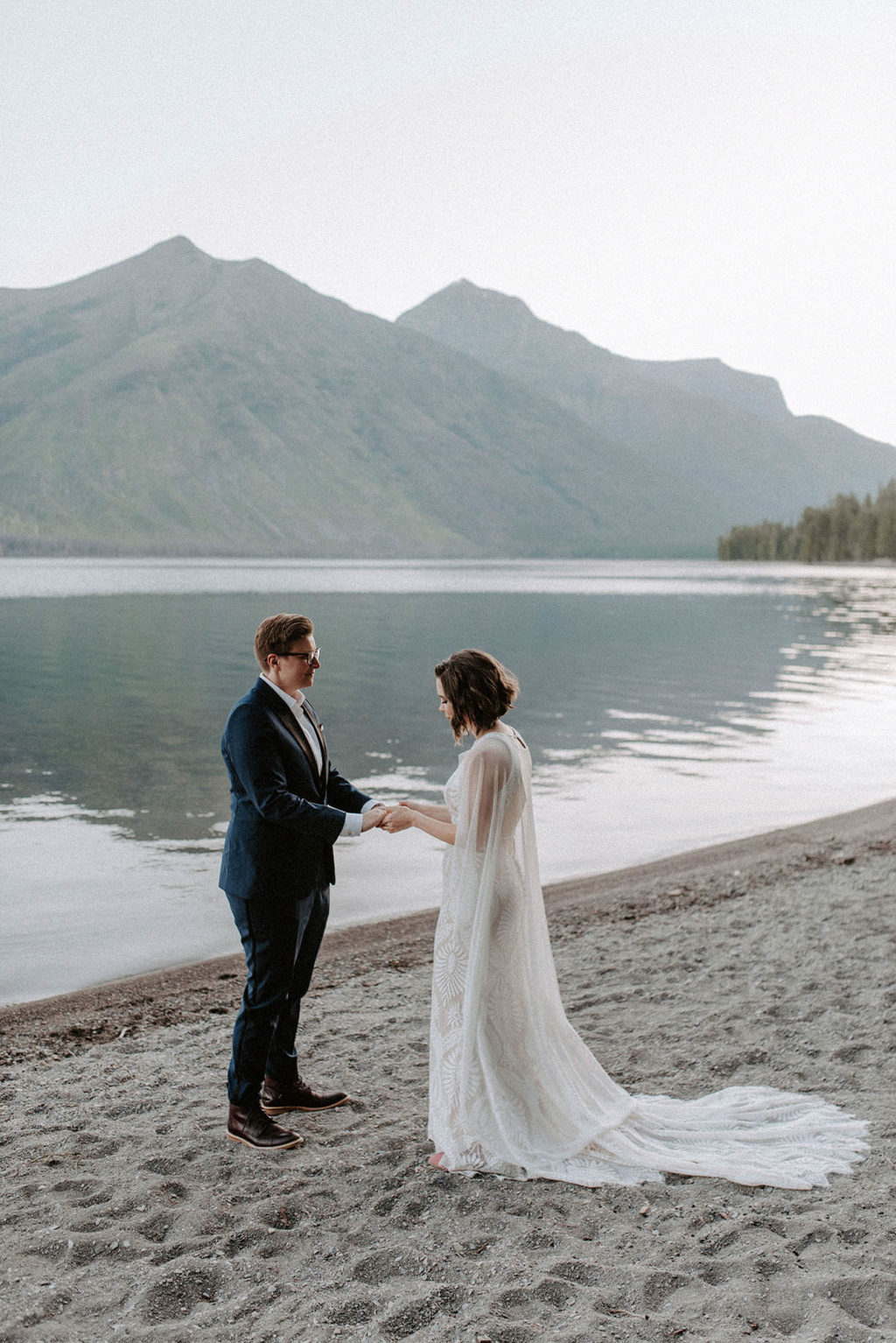 two brides hold hands in front of mountains and lake at Glacier National Park