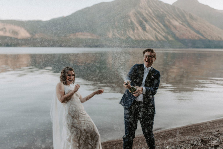 two brides spray champagne over the beach at Lake McDonald