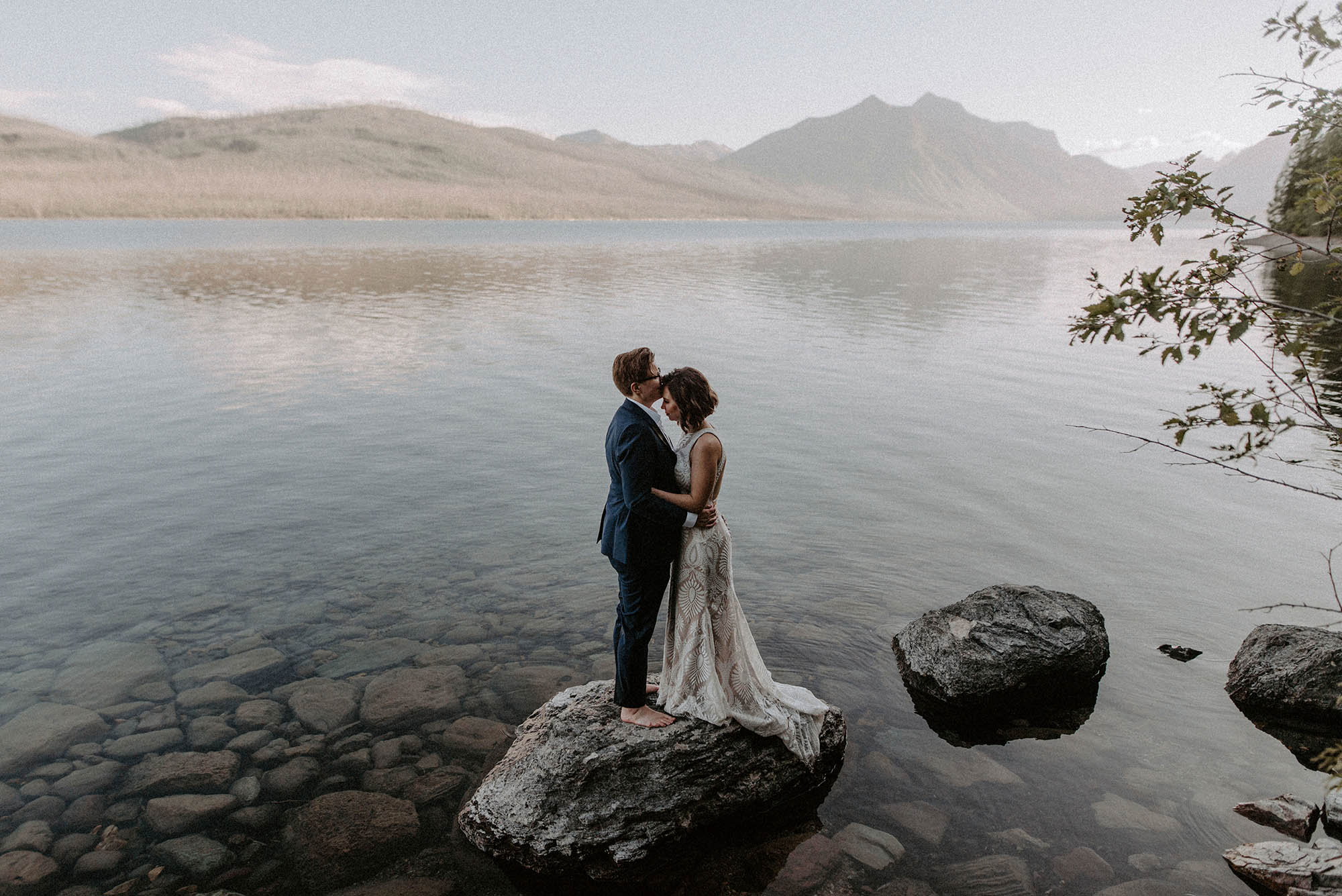 two brides standing on rock in Lake McDonald with mountains behind them
