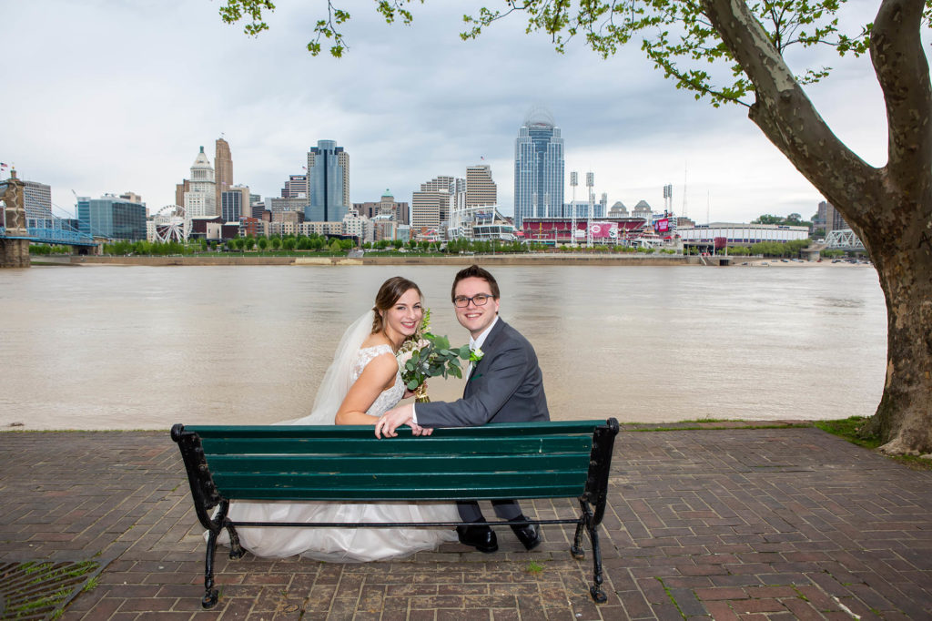 bride and groom at bench overlooking Cincinnati skyline