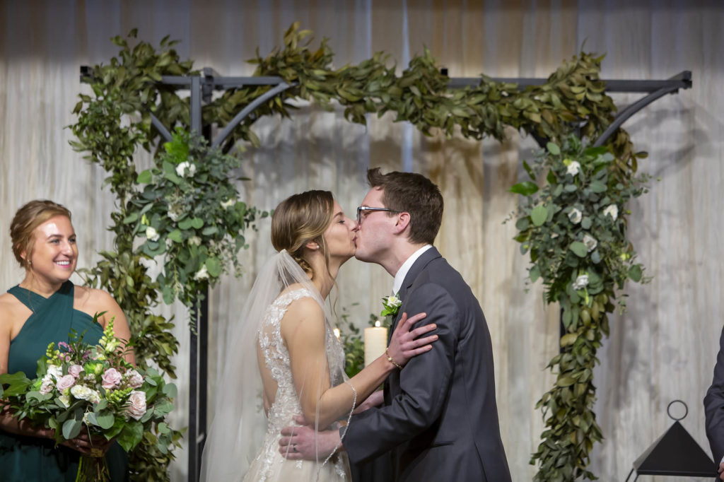 bride and groom kiss at end of wedding ceremony in front of floral arch at Madison Event Center