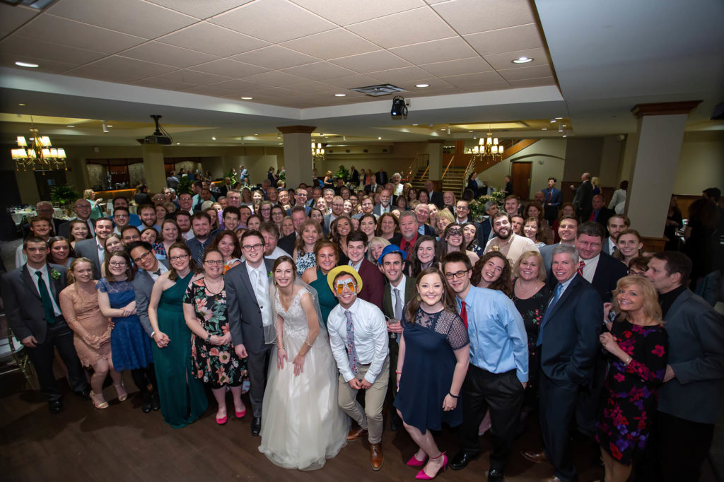 bride and groom with wedding guests group photo at Madison Event Center wedding