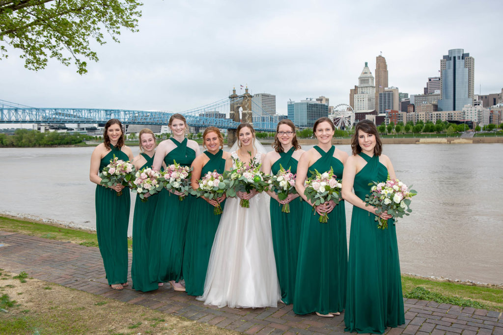 bride and with bridesmaids in green dresses holding pink and green bouquets at Cincinnati skyline
