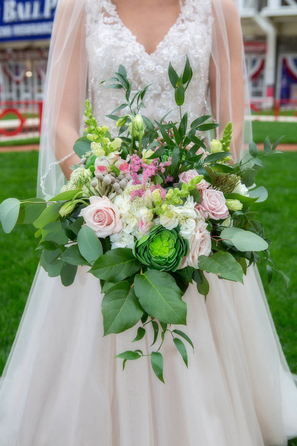 bride holding bouquet with pink and green flowers