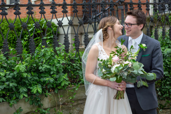 bride in sleeveless wedding gown and veil smiles at groom with glasses and green pocket square