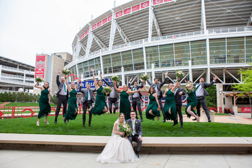 bridesmaids in green dresses groomsmen in gray suits jump up and down at Cincinnati Reds stadium after wedding