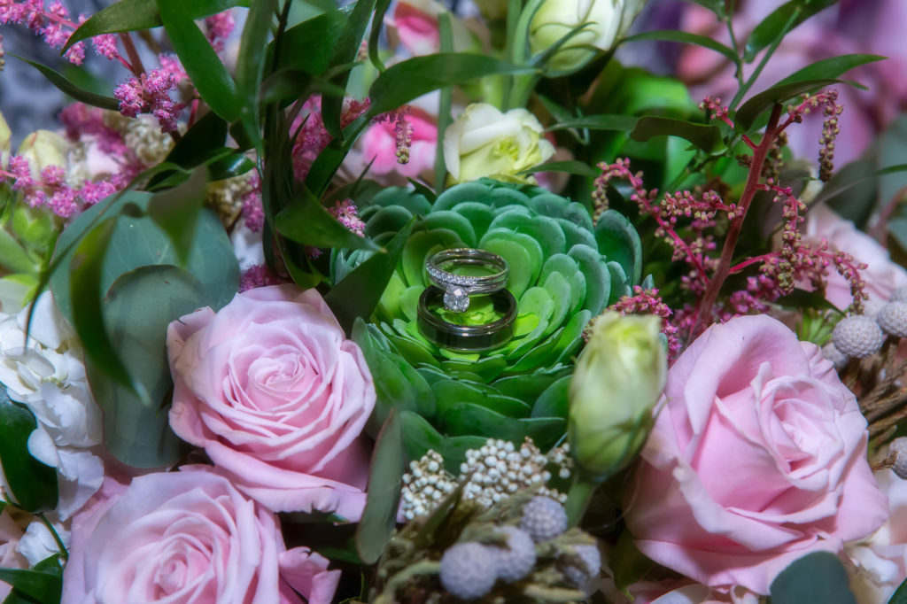 diamond engagement ring and wedding rings on pink and green bridal bouquet
