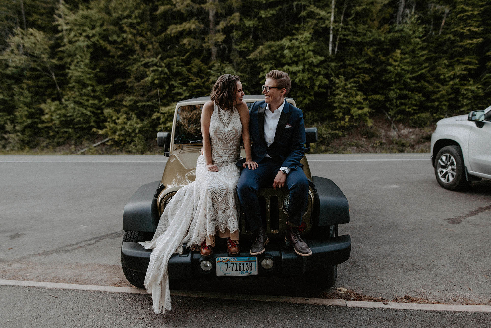 two brides sit on hood of Jeep in front of forest on wedding day