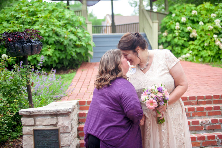 two brides touch foreheads after wedding ceremony